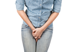 Close up of a woman with hands holding her crotch isolated in a white background